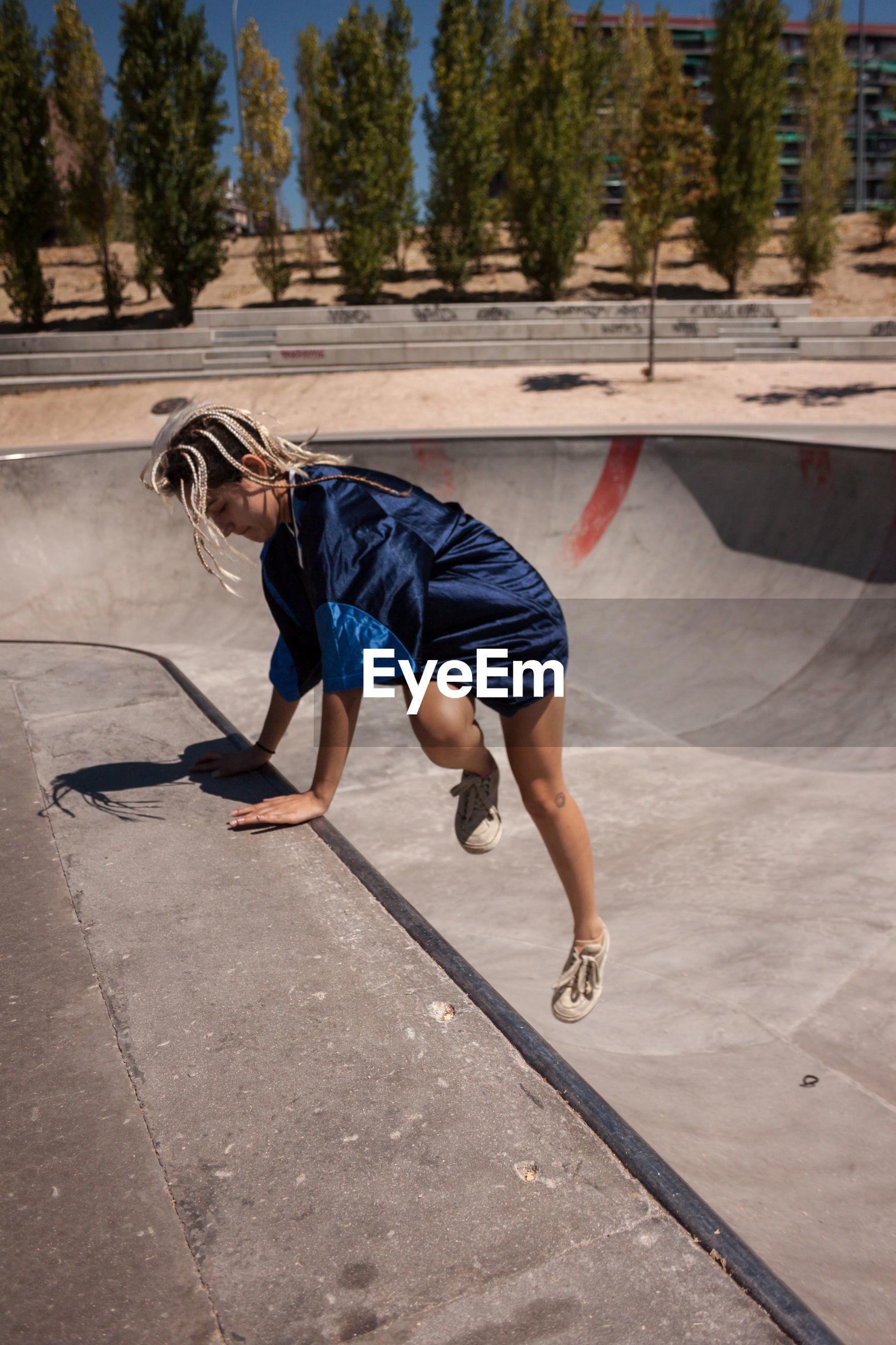 Full length of woman skateboarding at skateboard park