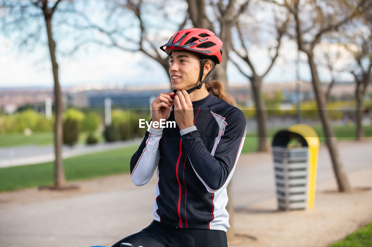 Young man wearing cycling helmet against trees