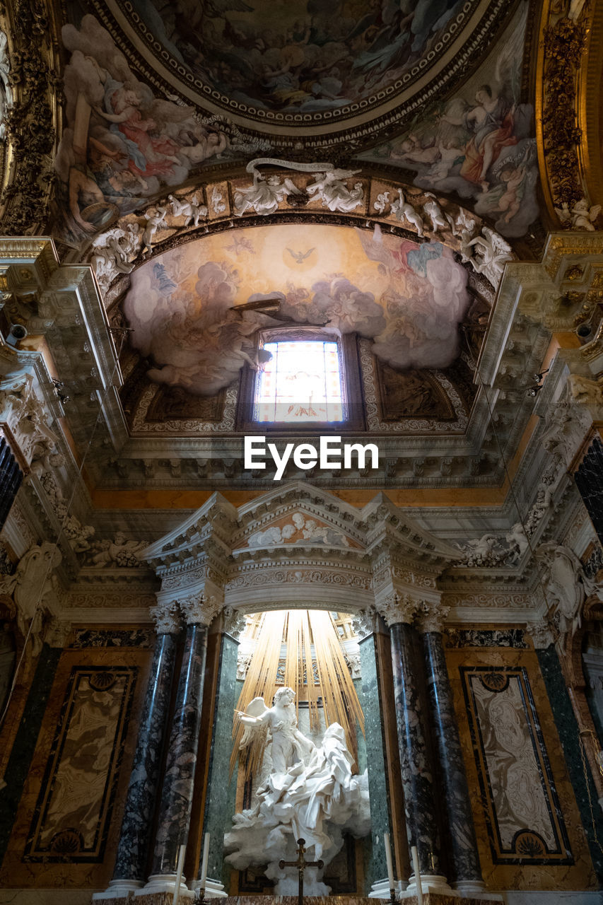 indoors, architecture, religion, place of worship, low angle view, spirituality, built structure, belief, human representation, ceiling, history, the past, art and craft, building, representation, no people, sculpture, mural, architectural column, cupola, altar, fresco, ornate