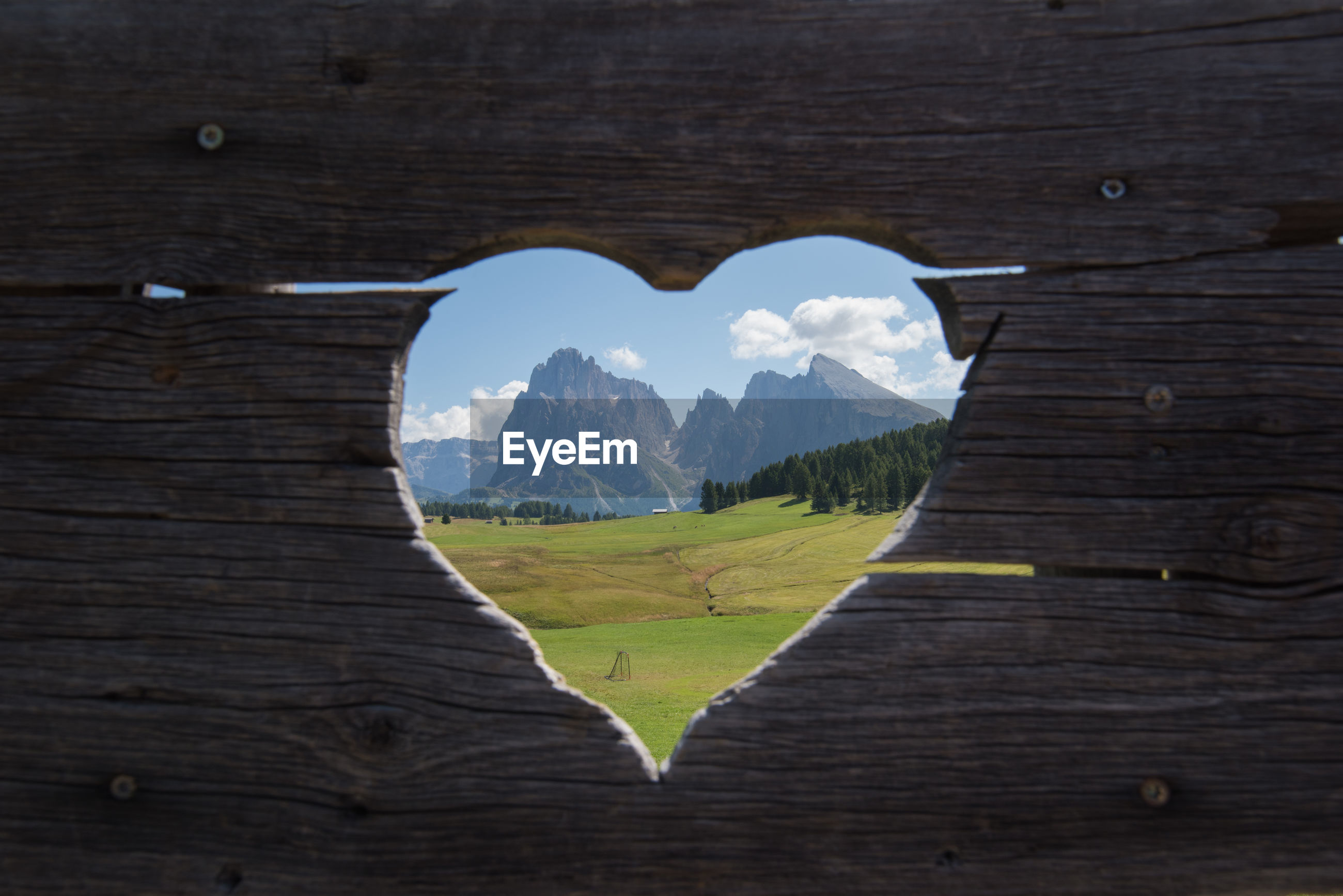 SCENIC VIEW OF LANDSCAPE SEEN THROUGH HOLE IN WOODEN WALL