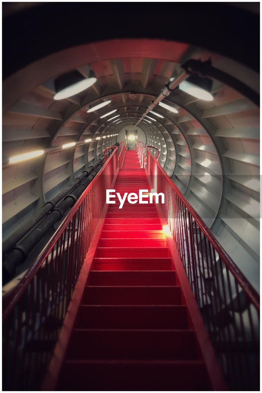 staircase, architecture, railing, the way forward, steps and staircases, illuminated, indoors, direction, red, transfer print, built structure, diminishing perspective, lighting equipment, auto post production filter, transportation, no people, empty, tunnel, modern, connection, ceiling, light, light at the end of the tunnel, underpass