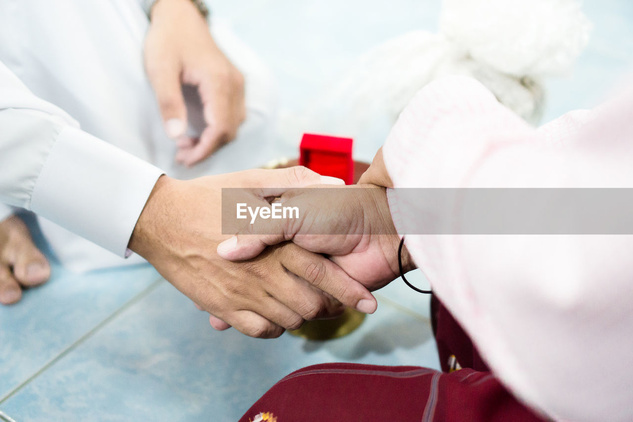 human hand, hand, real people, red, human body part, men, selective focus, adult, two people, holding, occupation, people, women, holding hands, close-up, love, midsection, togetherness, positive emotion, day, finger, wedding ceremony
