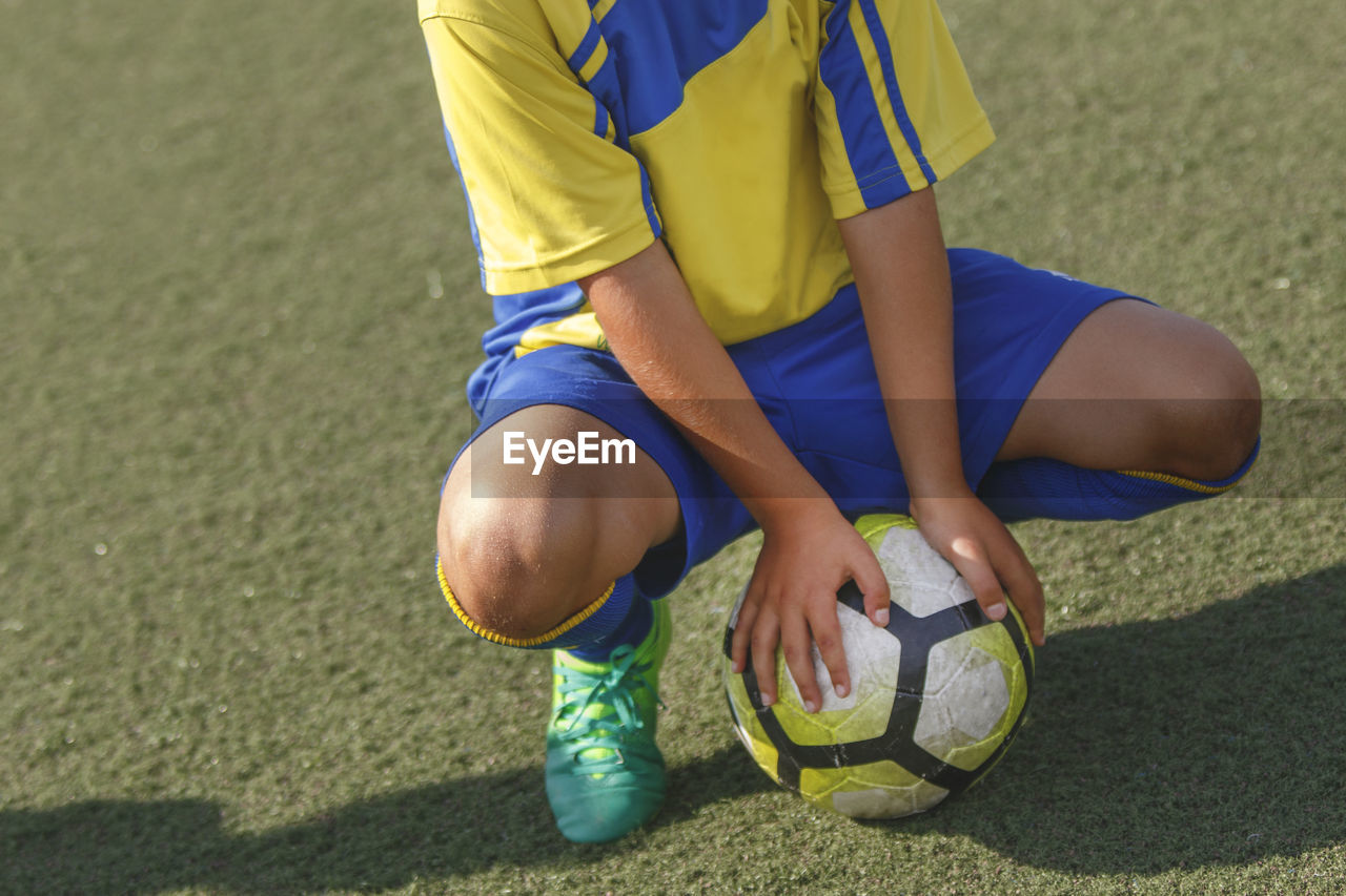Low Section Of Man With Soccer Ball Crouching On Field