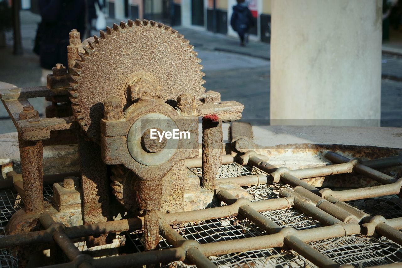 Close-Up Of Rusty Machine Part By Street