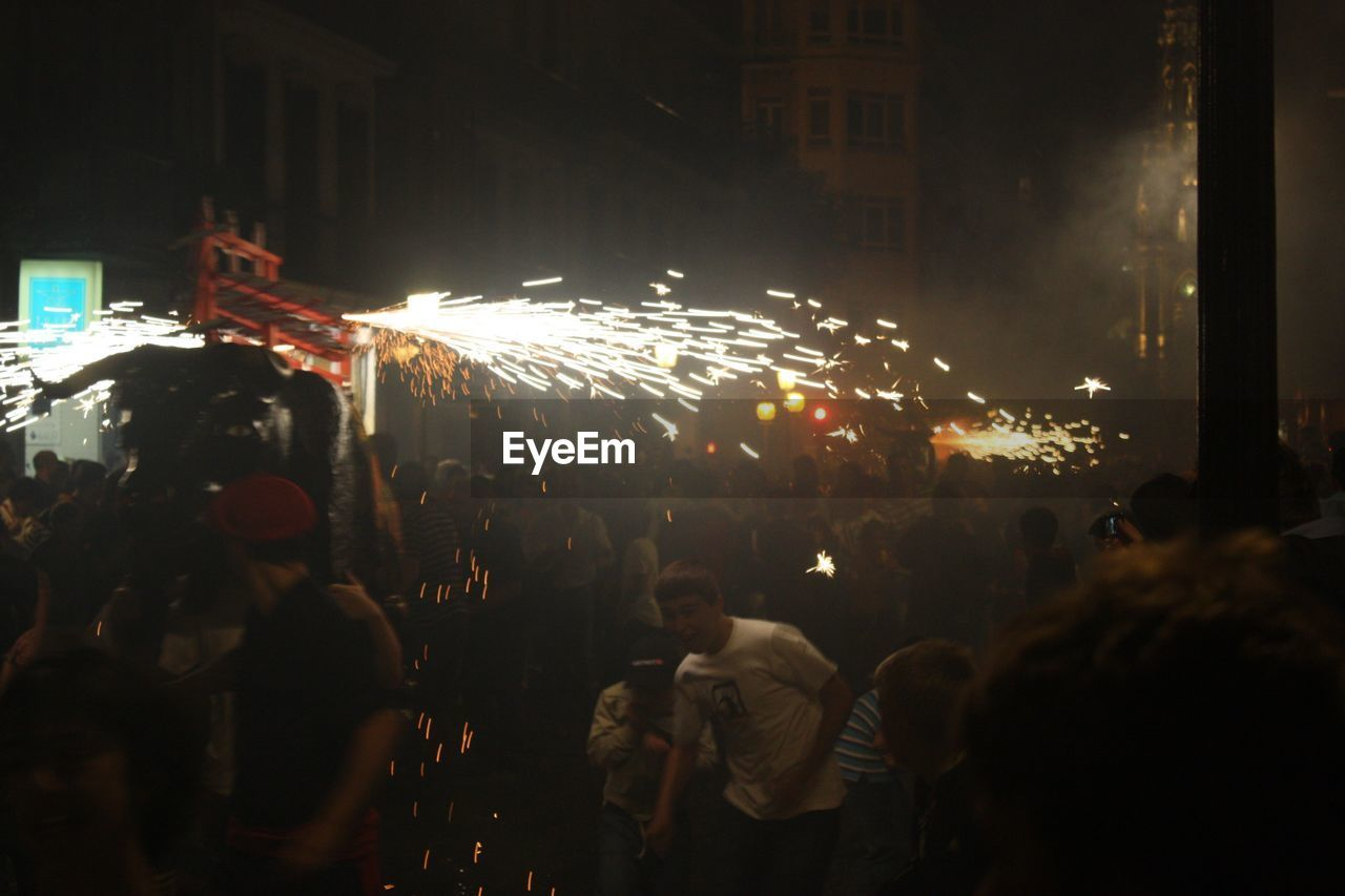 night, large group of people, celebration, illuminated, crowd, arts culture and entertainment, event, firework display, blurred motion, firework - man made object, enjoyment, outdoors, city, men, women, lifestyles, real people, audience, people, adult