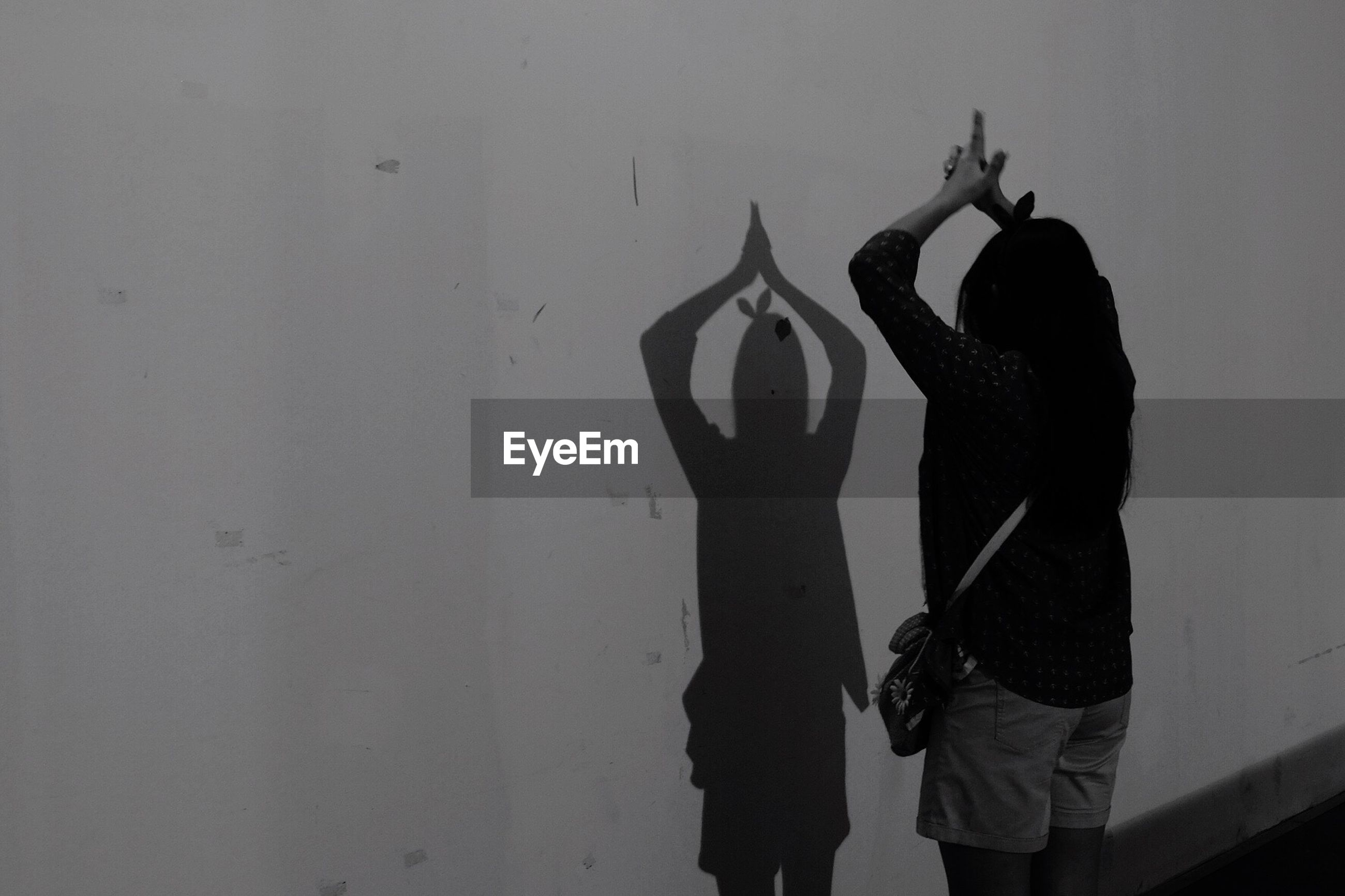 Rear view of woman standing with arms raised against shadow on wall