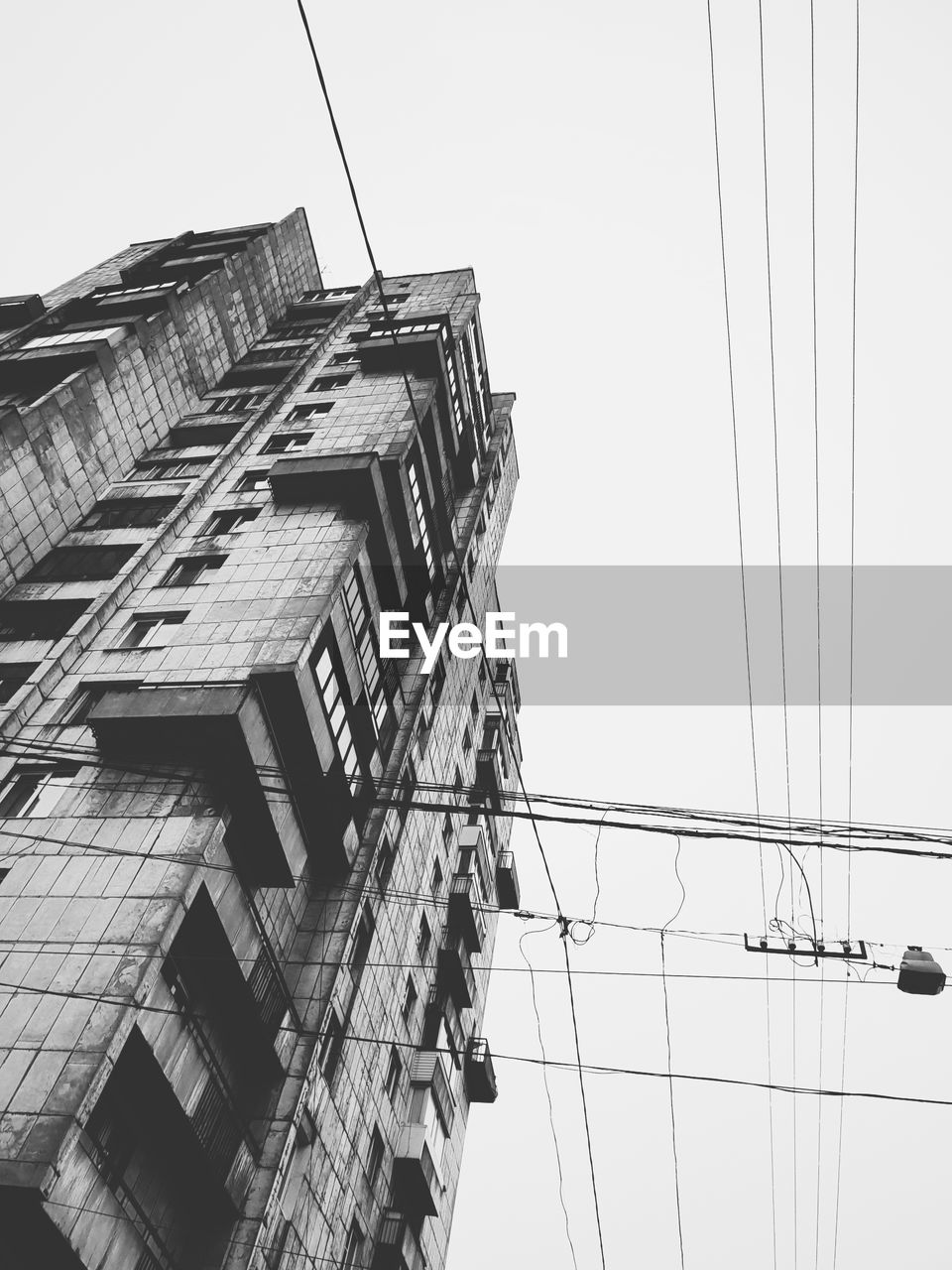low angle view, built structure, architecture, sky, building exterior, cable, clear sky, nature, day, building, no people, electricity, power line, outdoors, connection, city, residential district, technology, tall - high, power supply