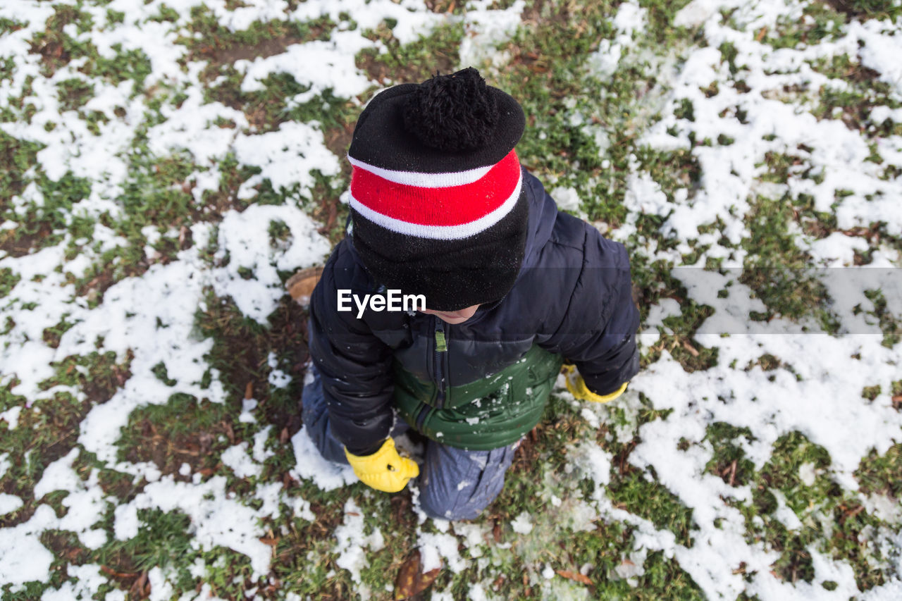 High Angle View Of Child In Warm Clothing On Snow Covered Field