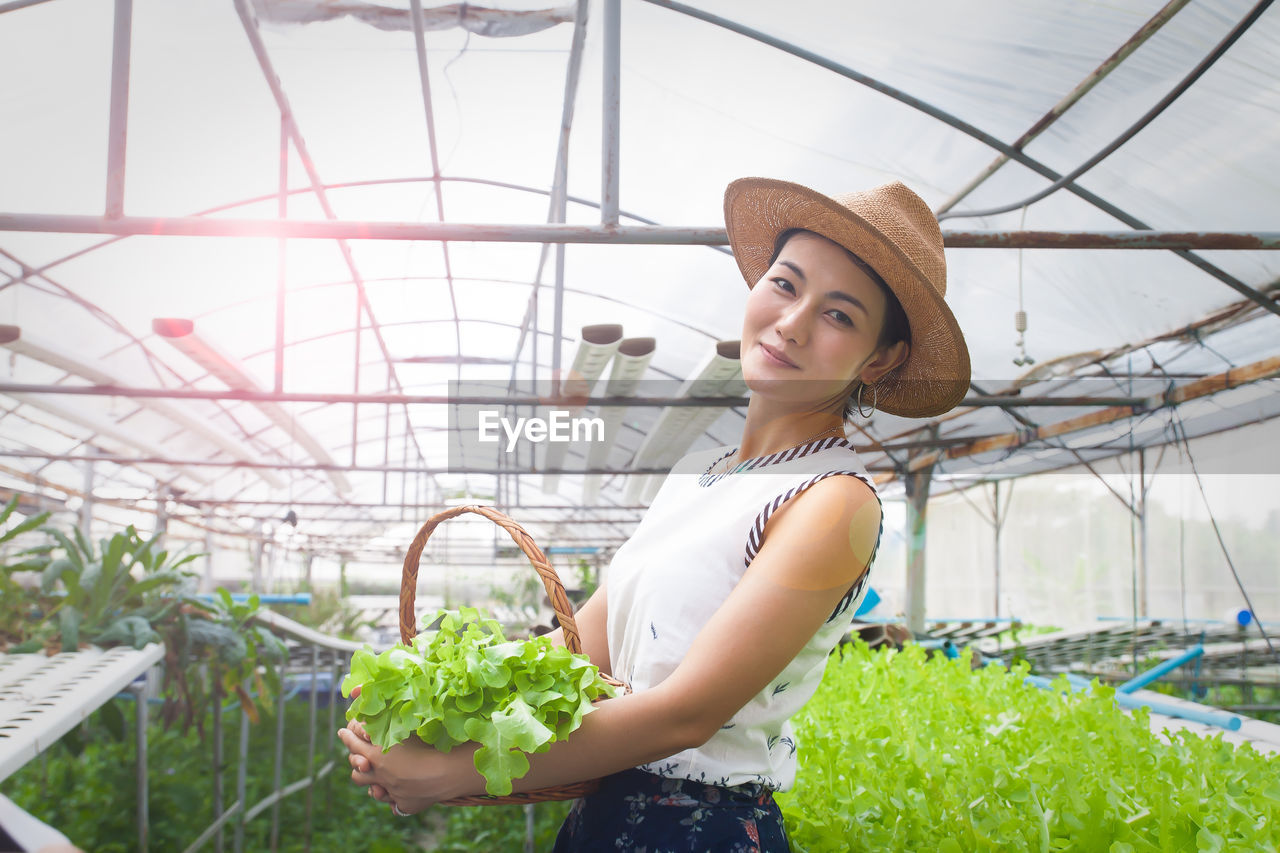 Portrait of woman holding vegetables while standing in greenhouse