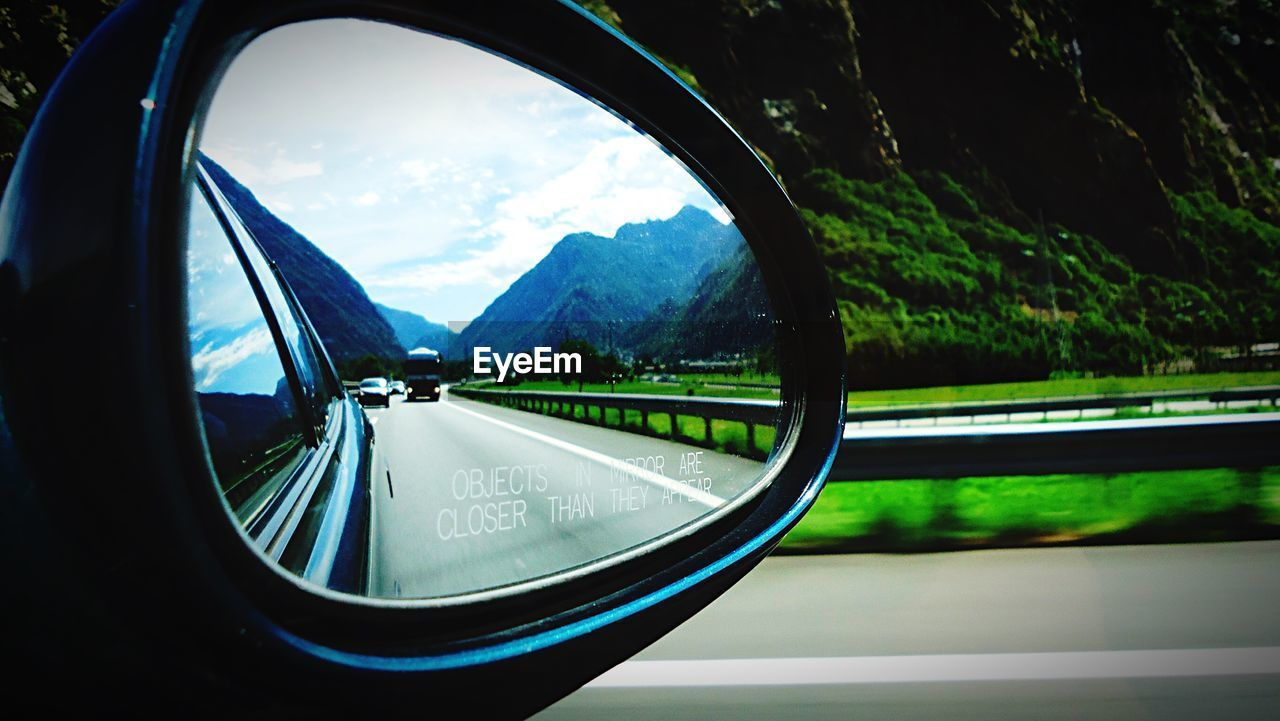 side-view mirror, transportation, reflection, mode of transport, car, land vehicle, window, nature, journey, no people, road, day, landscape, travel, beauty in nature, sky, tree, vehicle mirror, mountain, close-up, outdoors, scenics, water