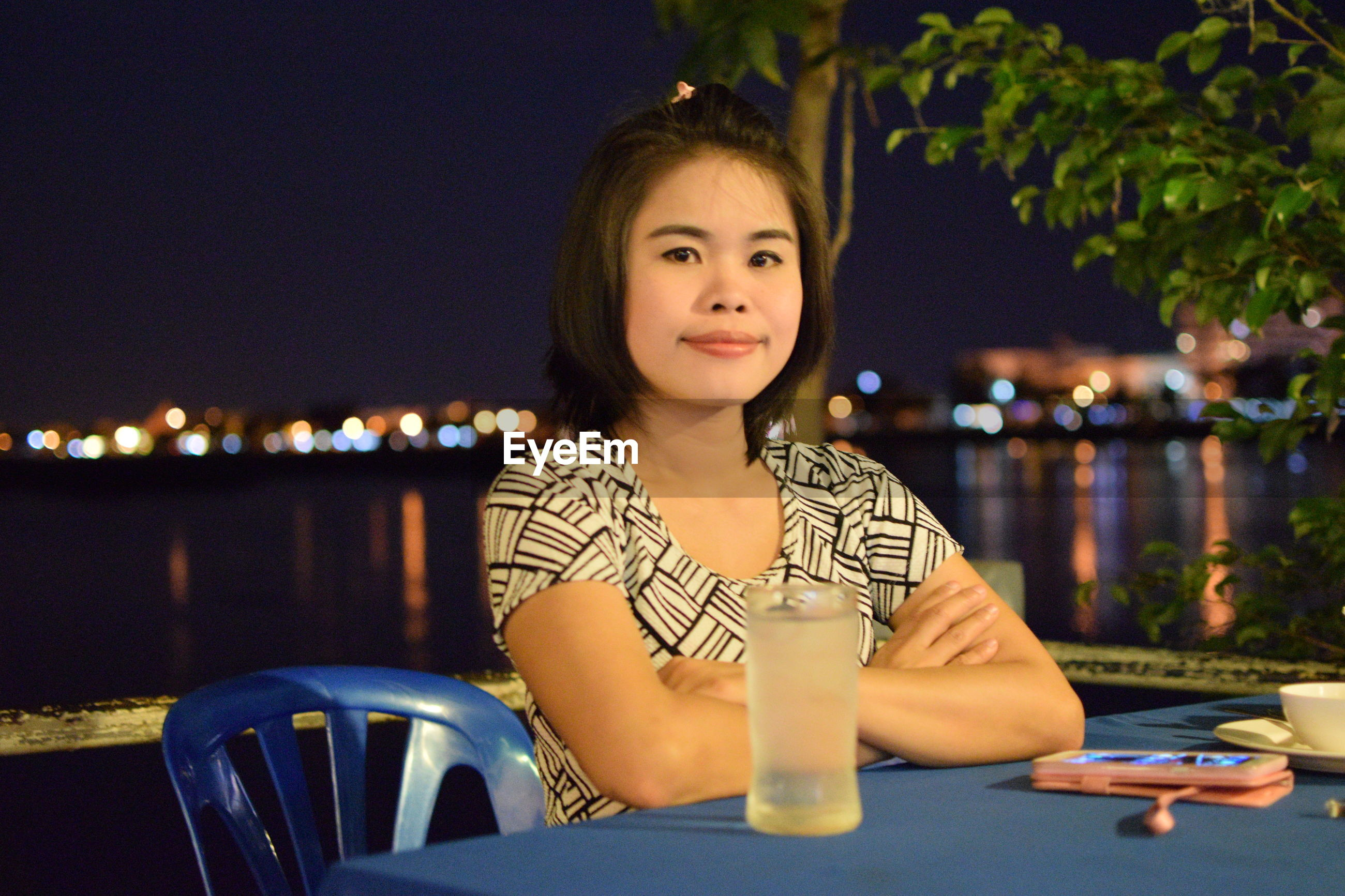 Portrait of young woman with arms crossed sitting against sea at outdoor cafe during night
