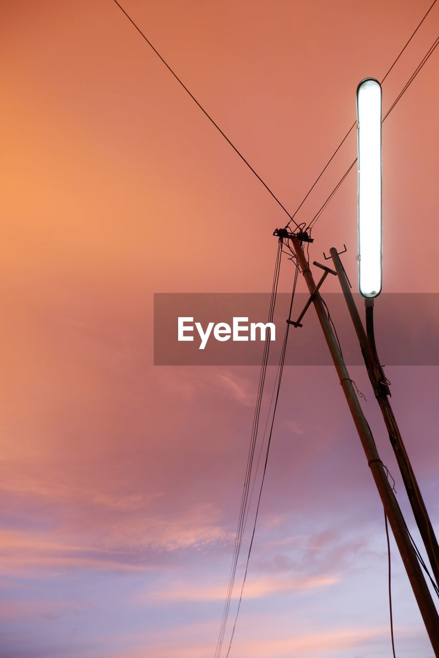 LOW ANGLE VIEW OF POWER LINES AGAINST ORANGE SKY