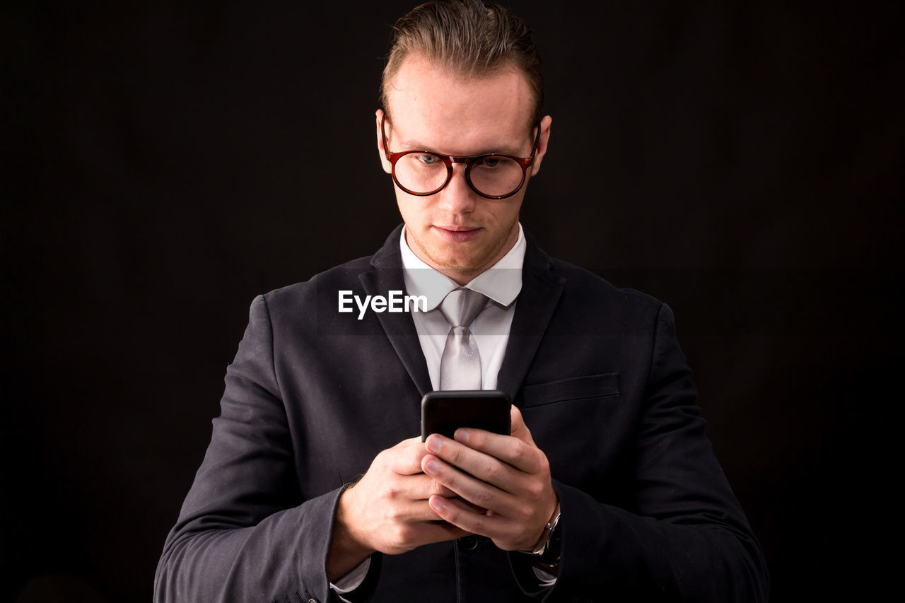Businessman using mobile phone against black background