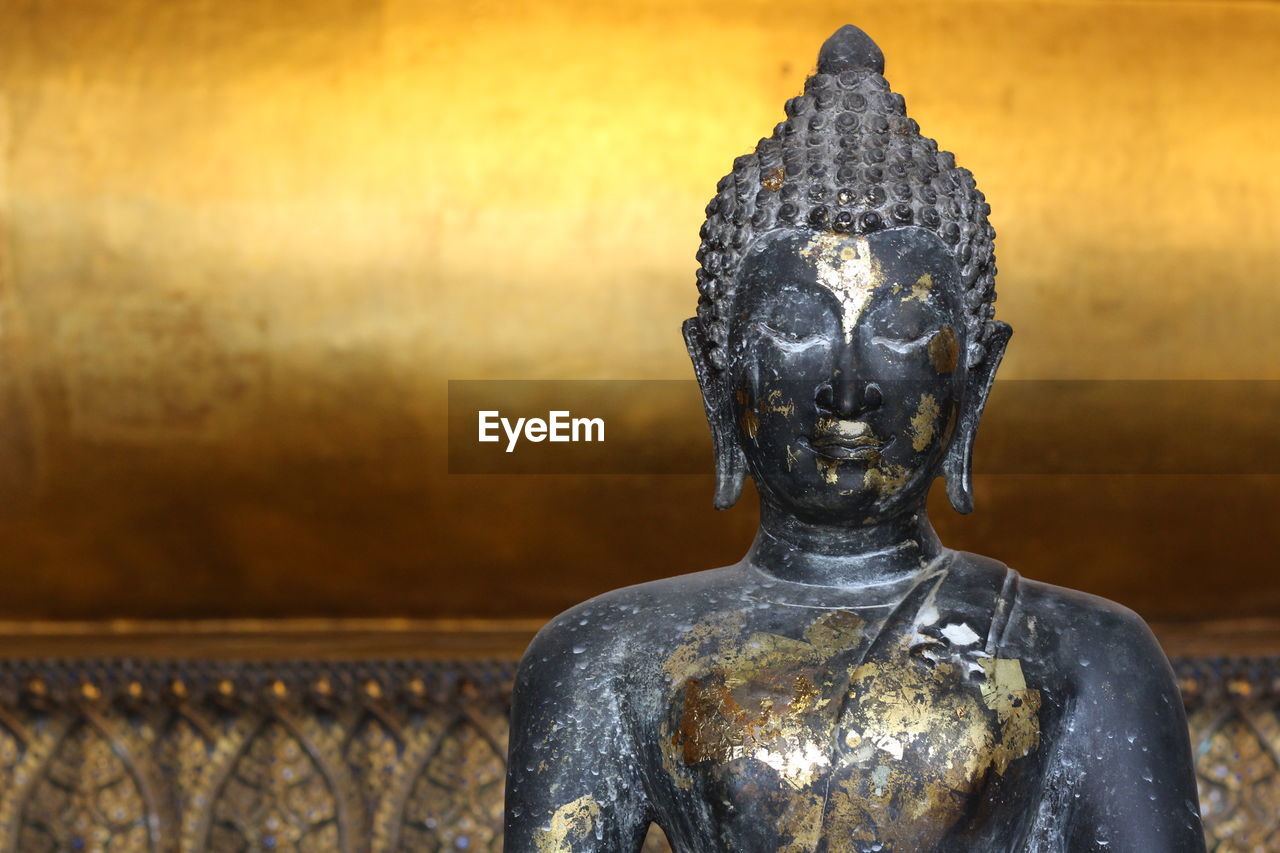 Close-Up Of Old Buddha Statue Against Golden Wall
