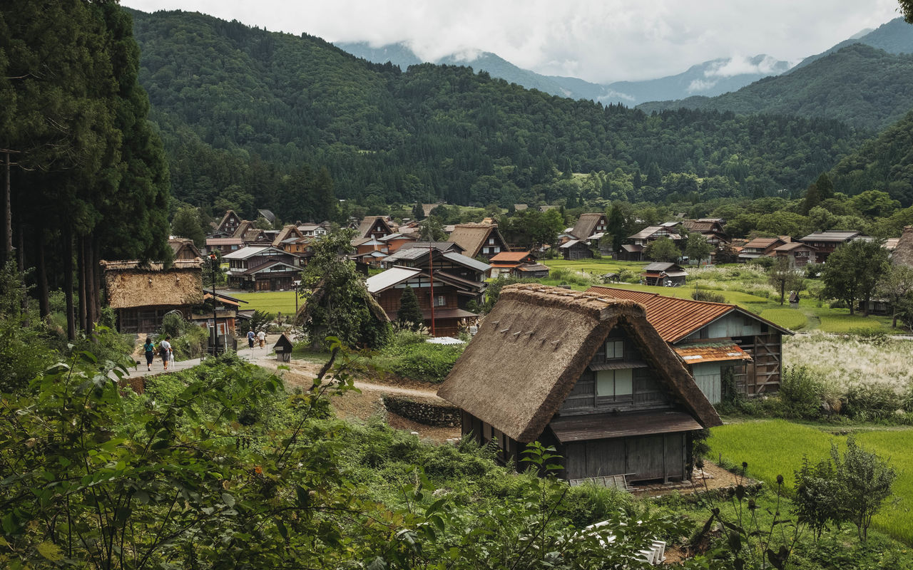 SCENIC VIEW OF VILLAGE BY HOUSES AND MOUNTAINS