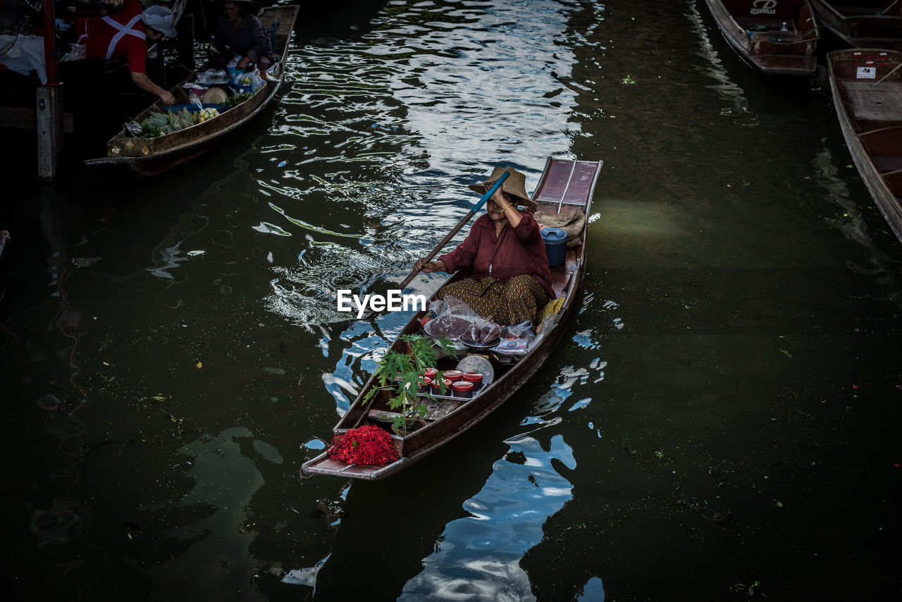 High angle view of woman on boat with vegetables in floating market