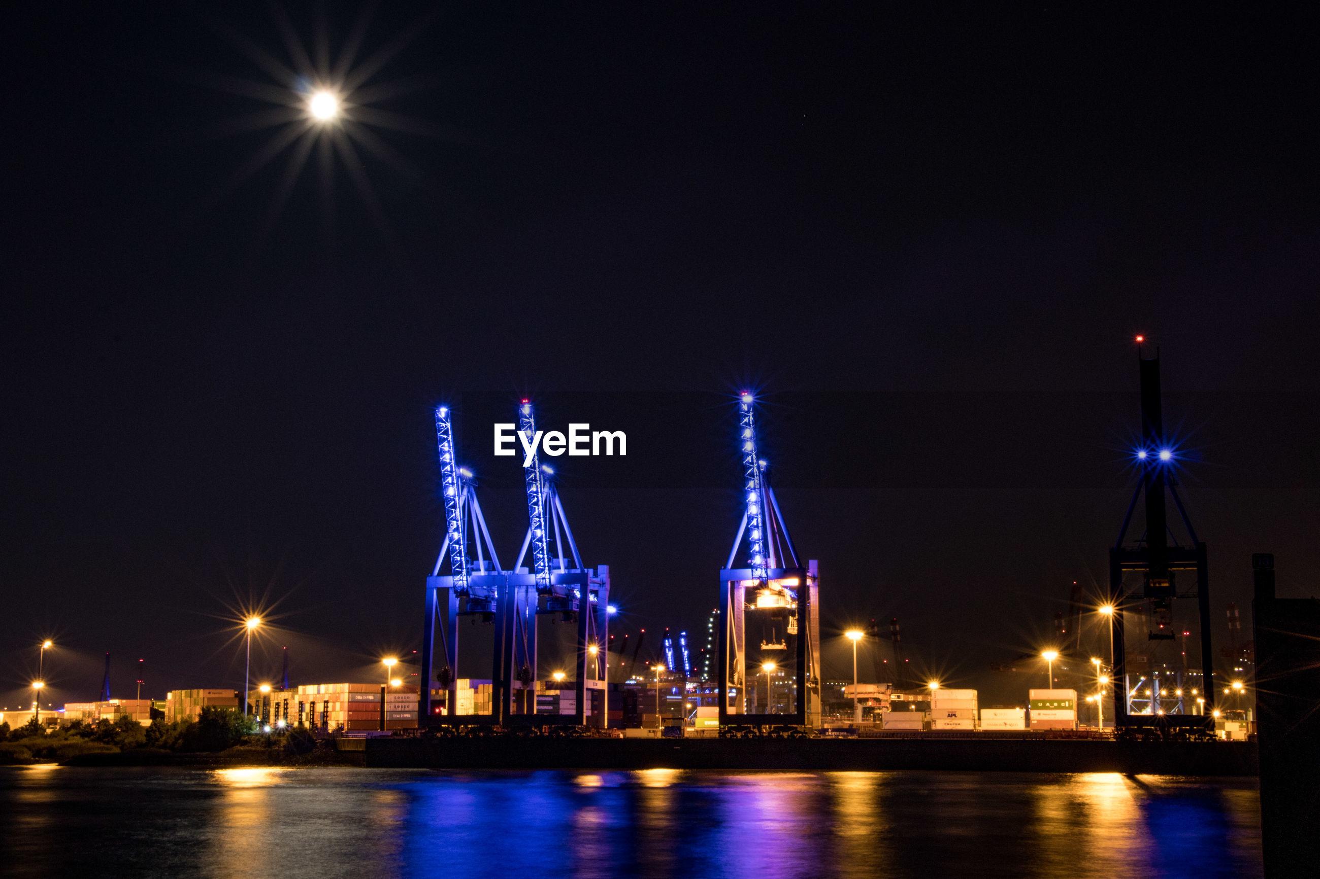 ILLUMINATED CITY SKYLINE AGAINST SKY AT NIGHT