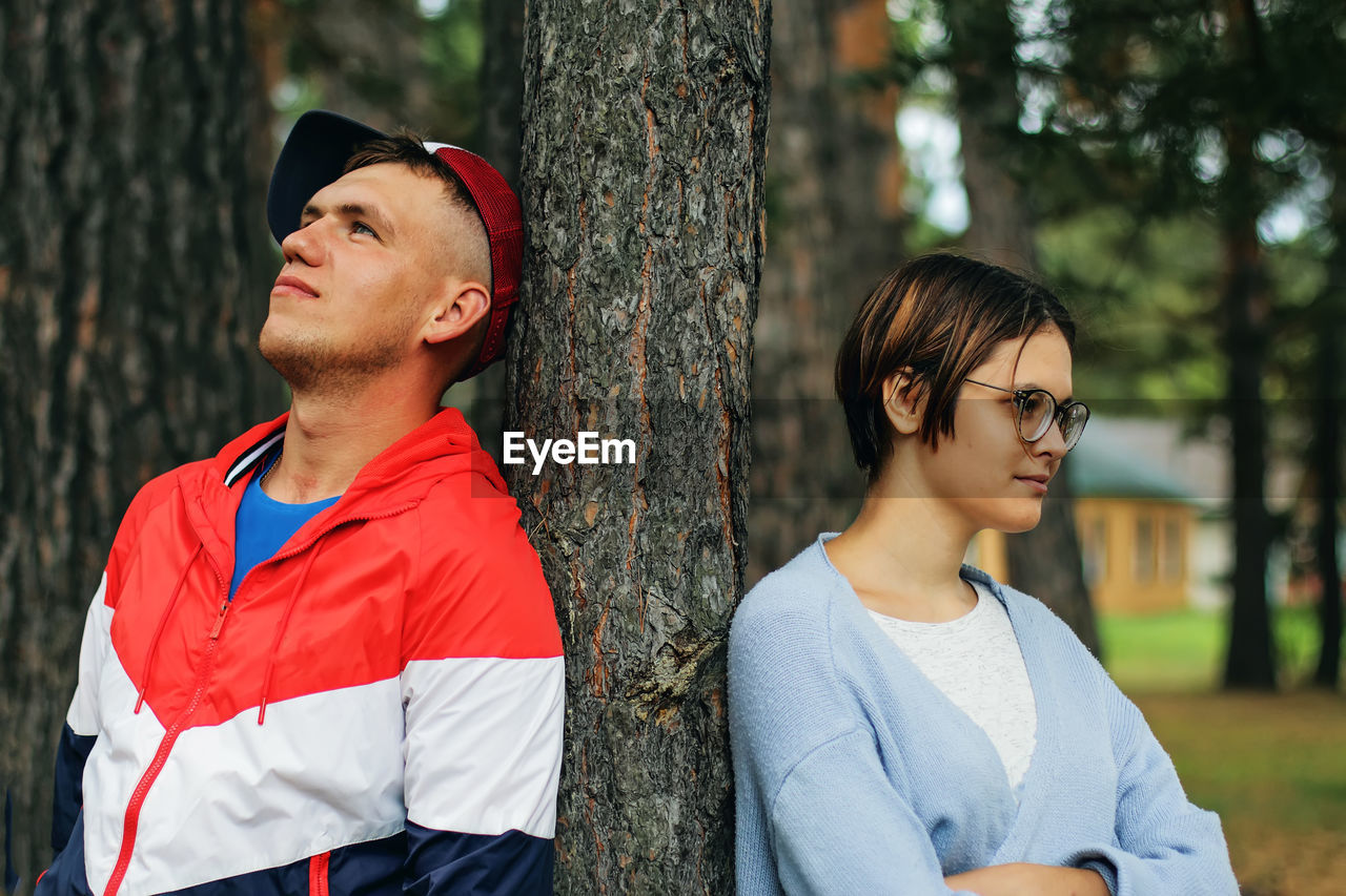 Couple standing by tree trunk at park