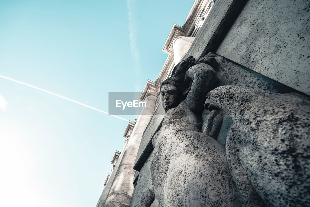 low angle view, built structure, sky, architecture, building exterior, nature, day, vapor trail, no people, art and craft, building, representation, sculpture, human representation, clear sky, male likeness, statue, sunlight, history, outdoors