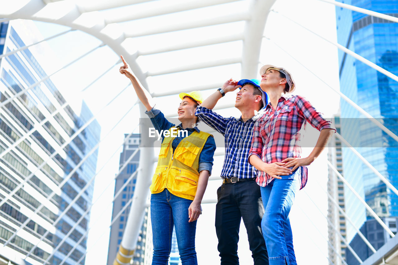 real people, architecture, standing, casual clothing, young adult, three quarter length, togetherness, built structure, group of people, young women, low angle view, young men, people, men, women, lifestyles, building exterior, day, teamwork, coworker