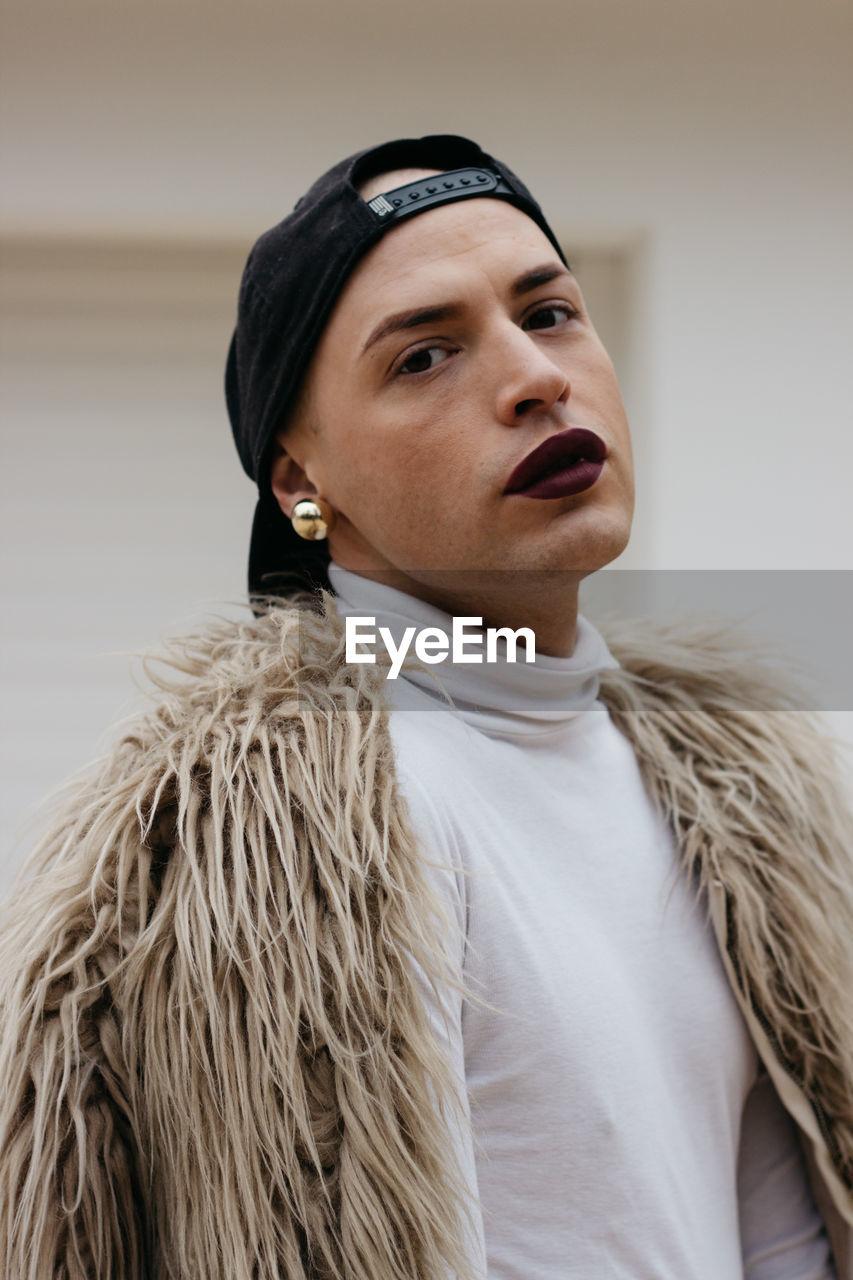 Close-Up Portrait Of Transgender Man Wearing Cap With Fake Fur