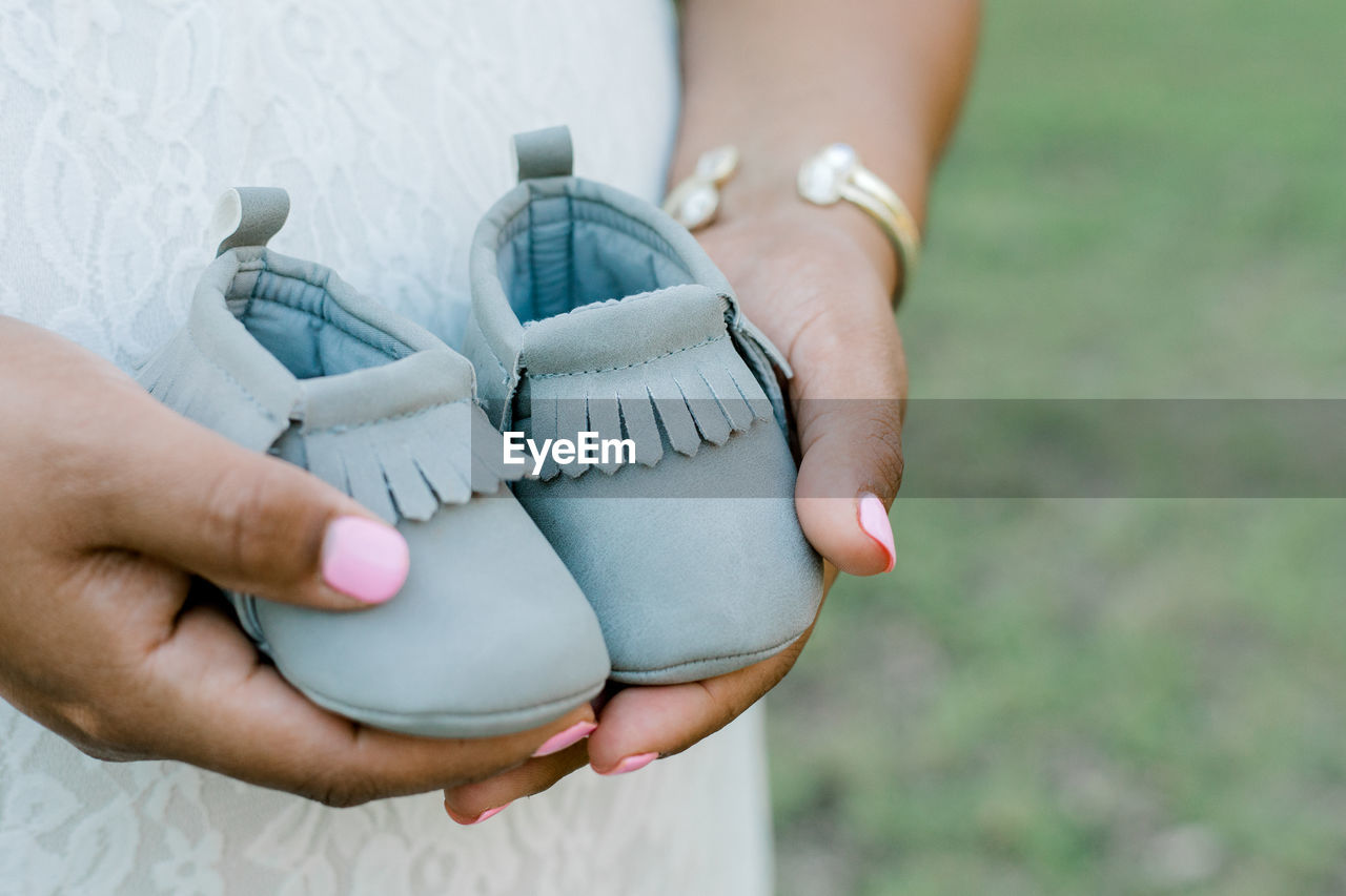 Midsection of pregnant woman holding shoes