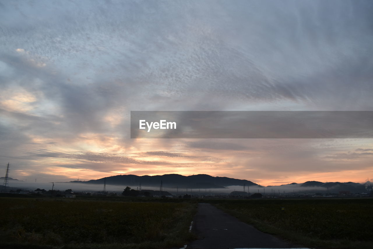 cloud - sky, sky, sunset, scenics - nature, beauty in nature, tranquil scene, road, no people, landscape, nature, environment, tranquility, transportation, the way forward, orange color, field, non-urban scene, direction, mountain, outdoors