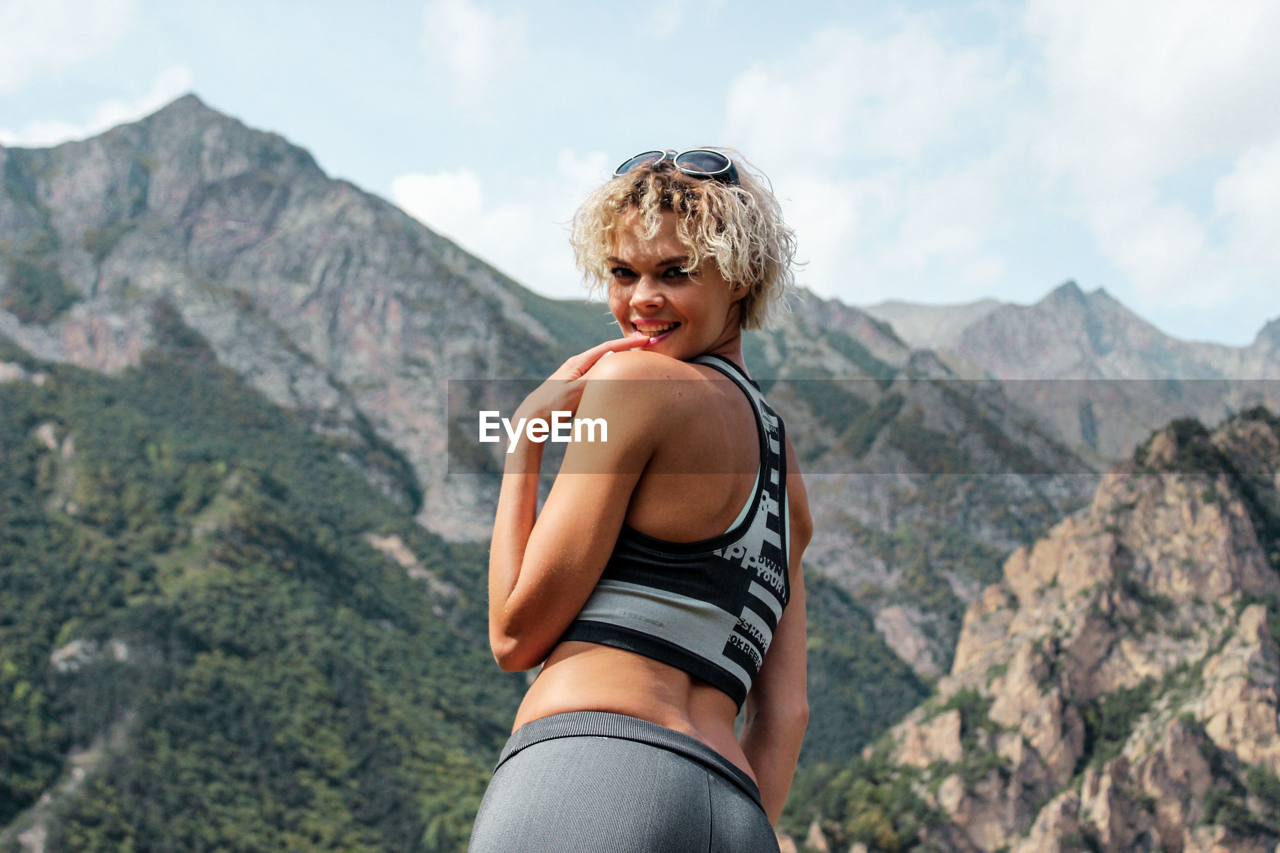 Portrait of smiling young woman standing against mountain range