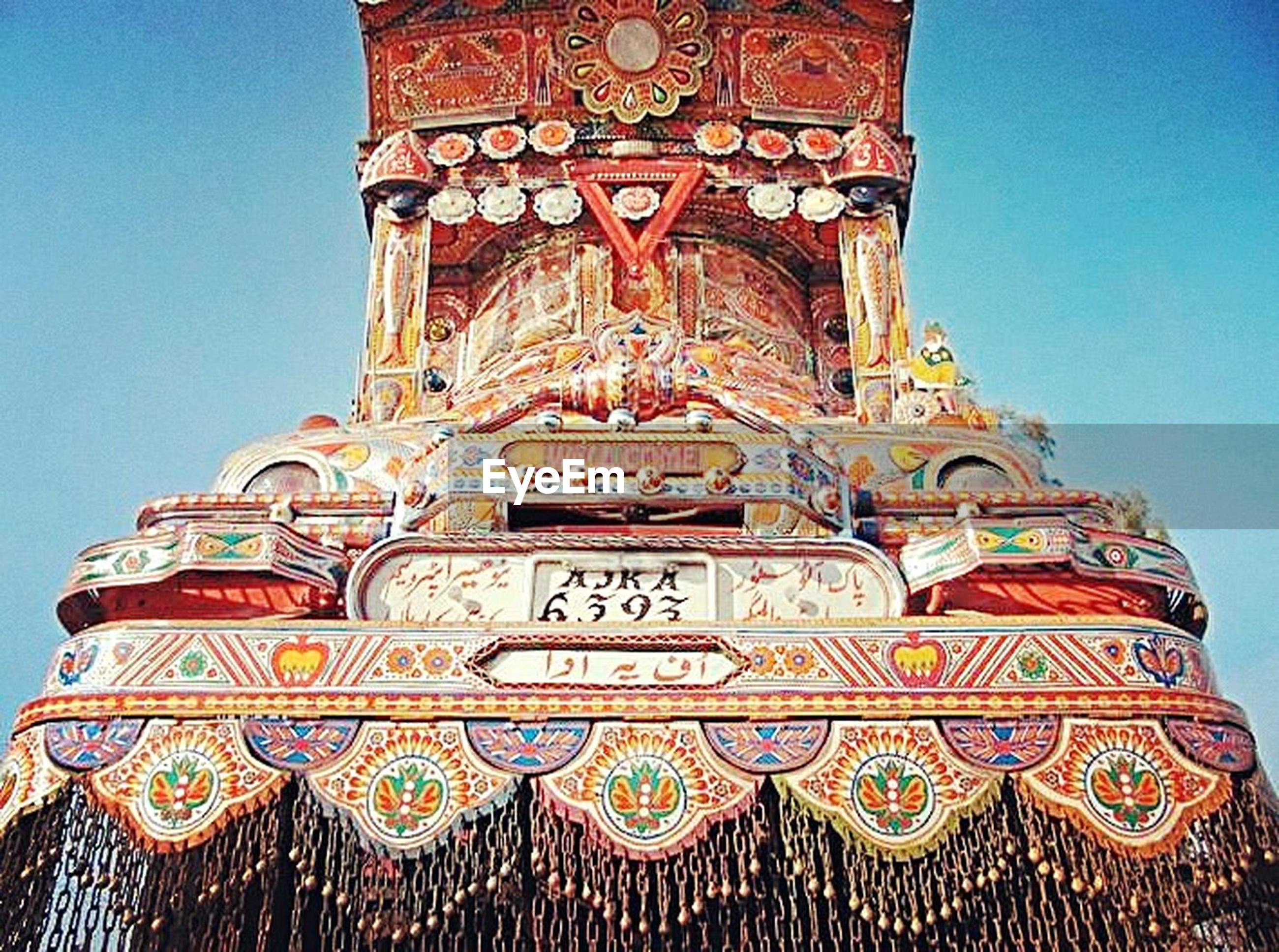 low angle view, religion, architecture, art and craft, spirituality, place of worship, clear sky, art, built structure, building exterior, famous place, blue, creativity, human representation, travel destinations, ornate, design, temple, carving - craft product