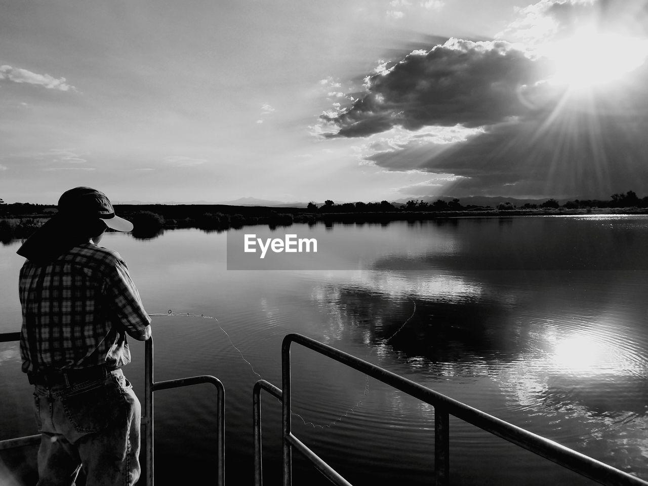 Man Fishing At Lake Against Sky