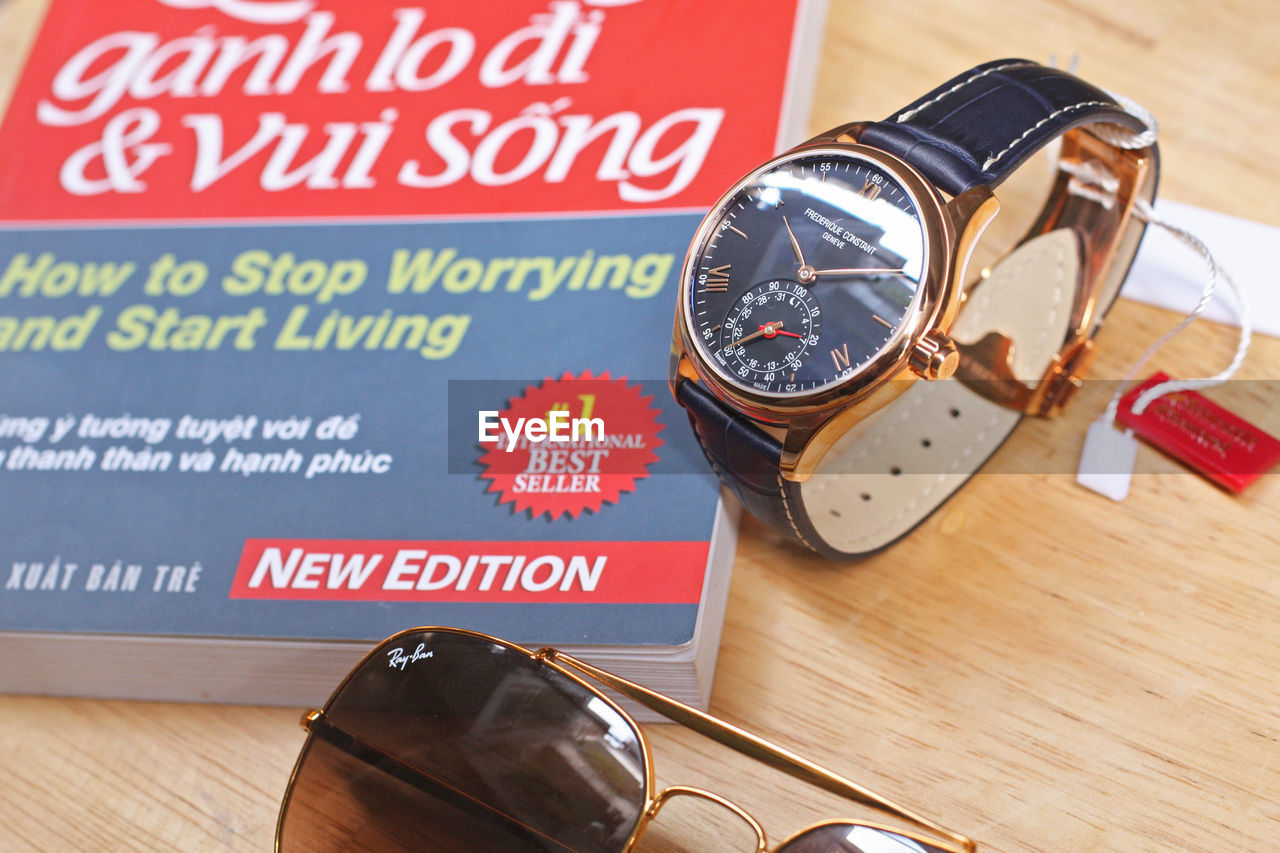 text, western script, communication, table, indoors, high angle view, still life, wood - material, no people, close-up, focus on foreground, time, personal accessory, number, fashion, technology, cigarette, non-western script, wristwatch