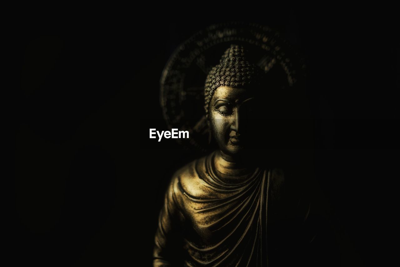 Close-Up Of Buddha Statue Against Black Background