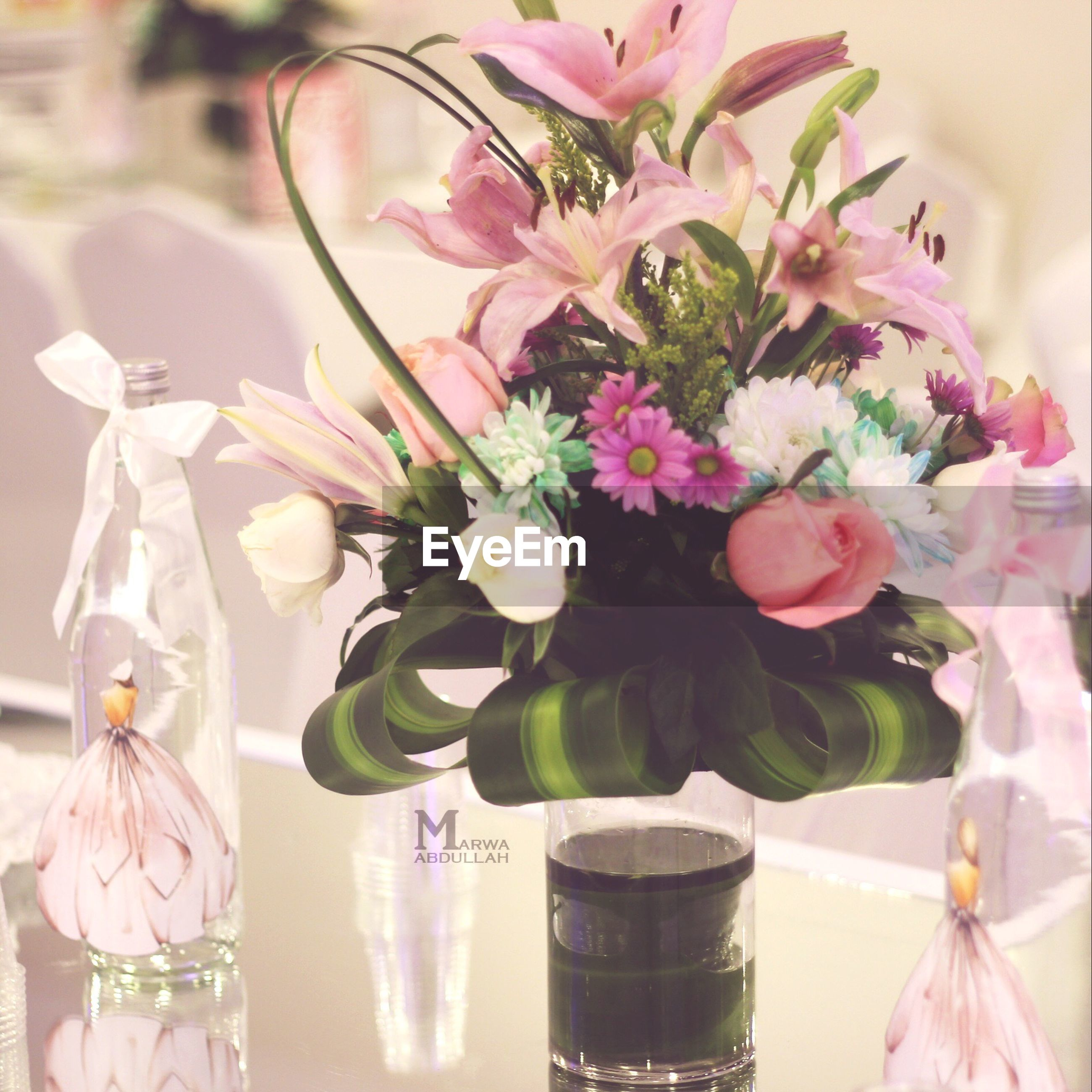 flower, indoors, freshness, vase, fragility, petal, decoration, flower arrangement, glass - material, close-up, table, pink color, flower head, still life, beauty in nature, bouquet, variation, bunch of flowers, focus on foreground, nature