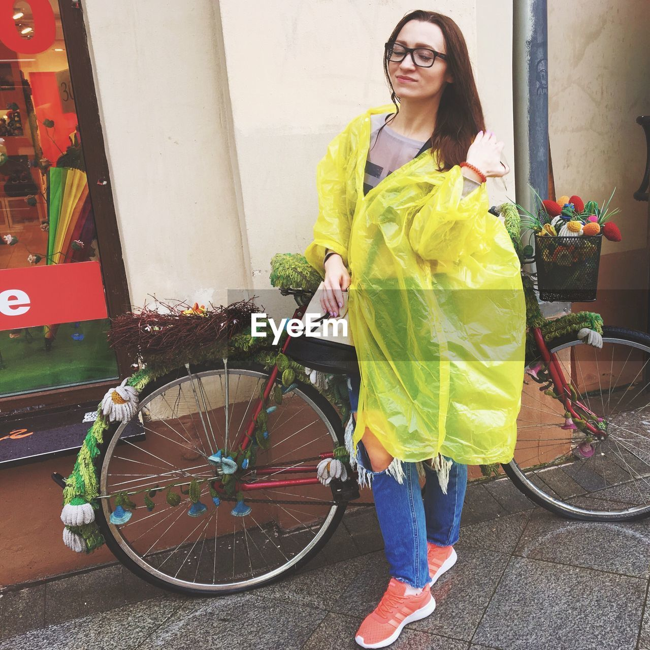 Woman wearing yellow raincoat standing by bicycle against wall