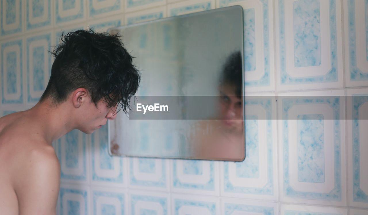 Shirtless man looking at his reflection in mirror at bathroom