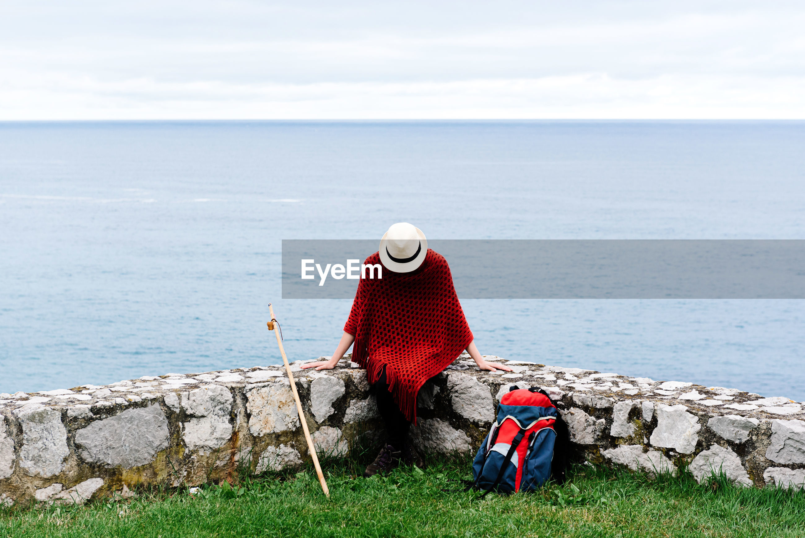 REAR VIEW OF PERSON LOOKING AT SEA