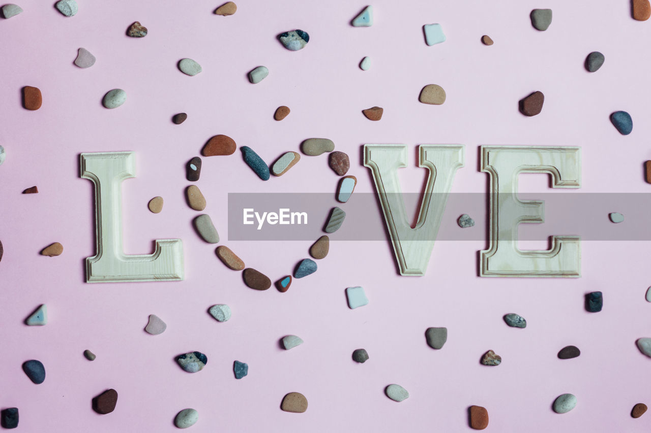 Directly above shot of love text with pebbles on table