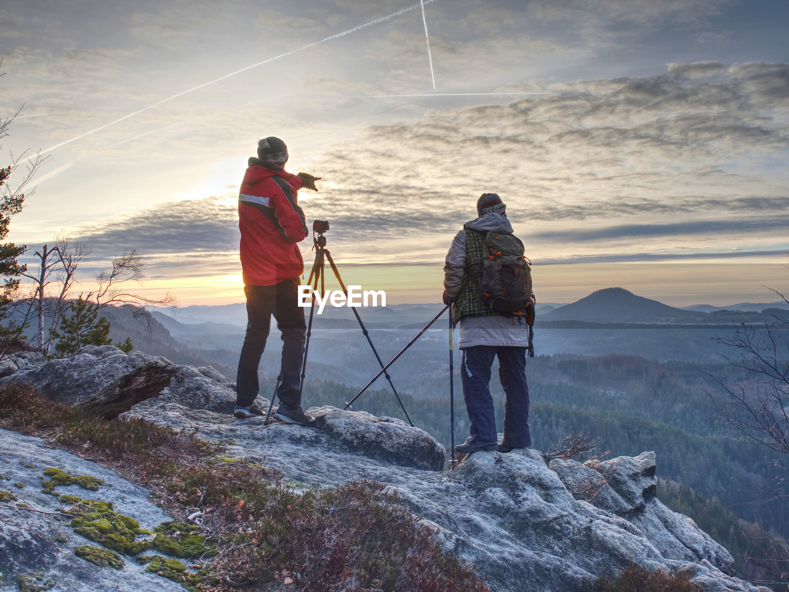Nature travel photographers in red and light jacket taking photo of autumnal landscape