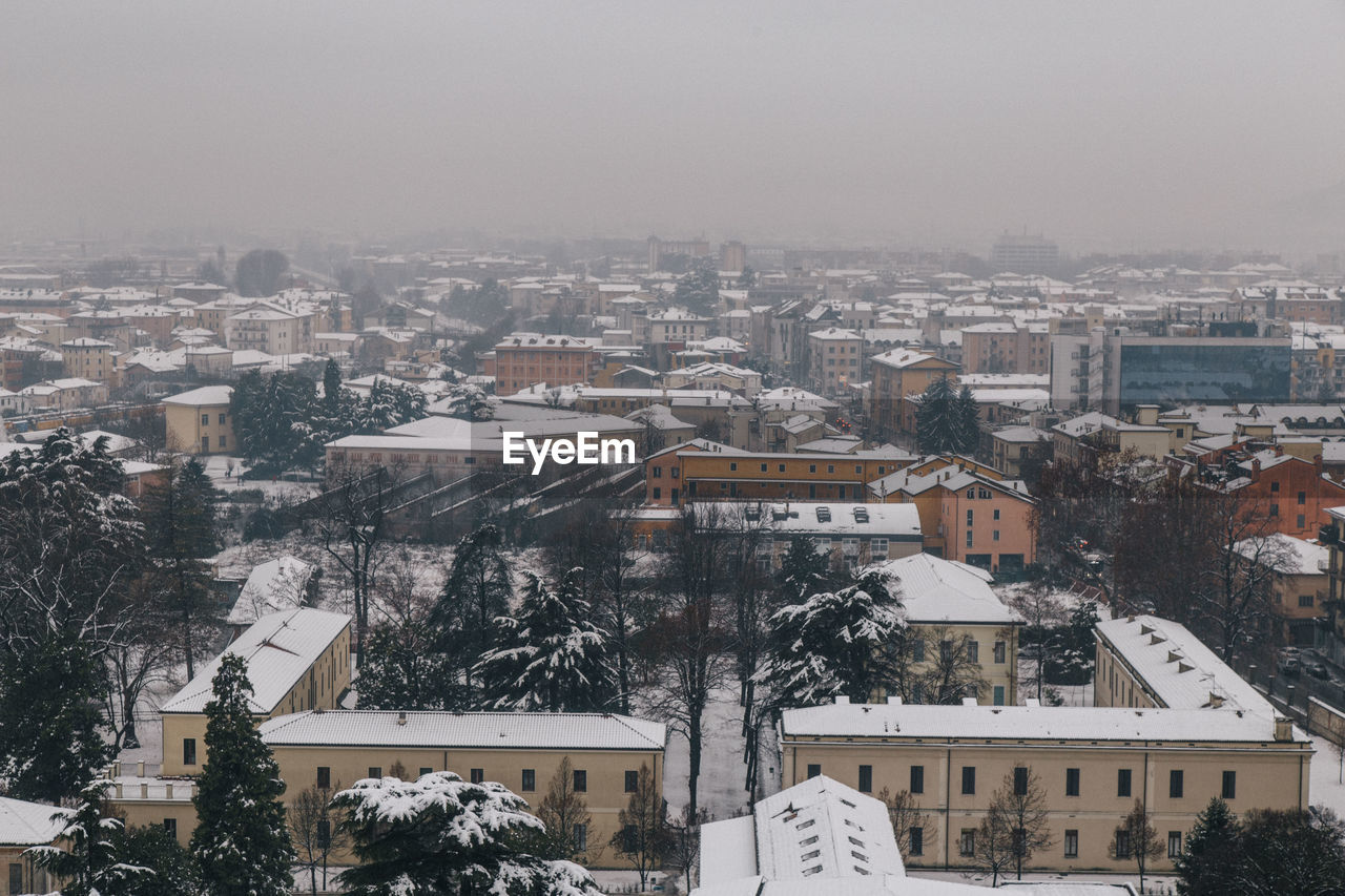 building exterior, architecture, built structure, winter, snow, cold temperature, residential building, house, residential district, weather, cityscape, no people, high angle view, outdoors, town, day, roof, city, nature, tree, sky