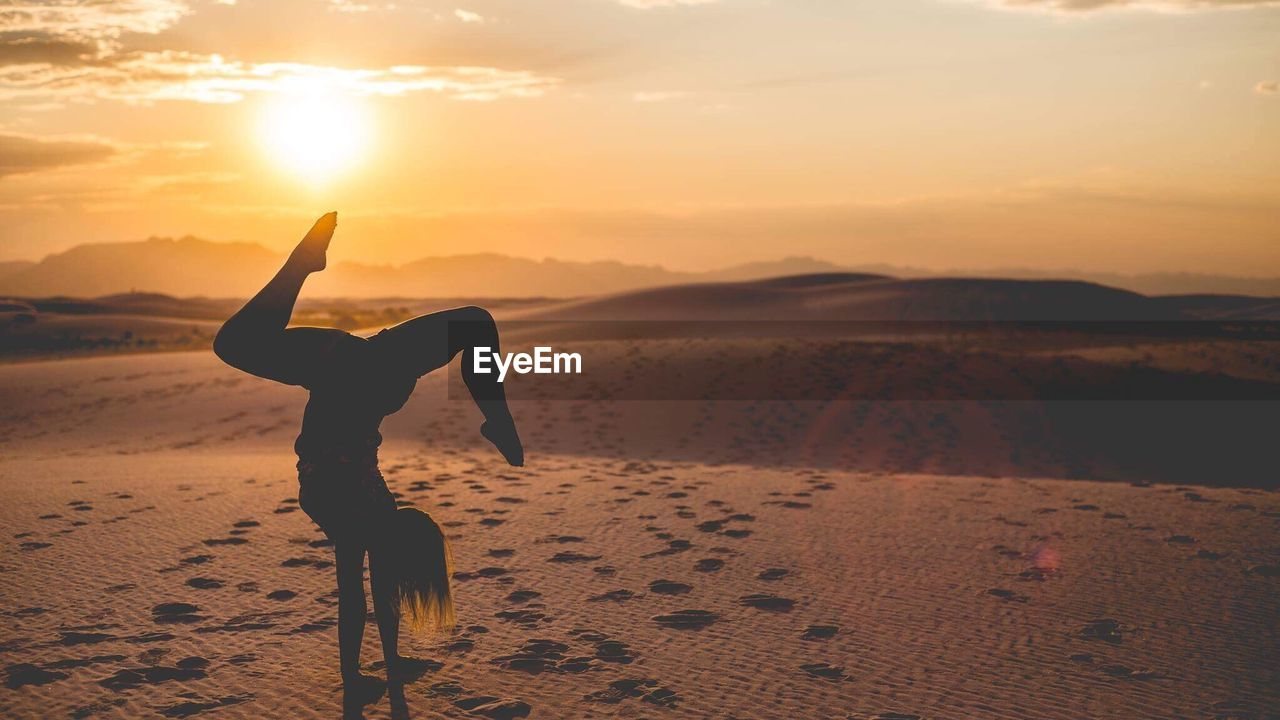 Silhouette Woman On Sand At Desert Against Sky During Sunset