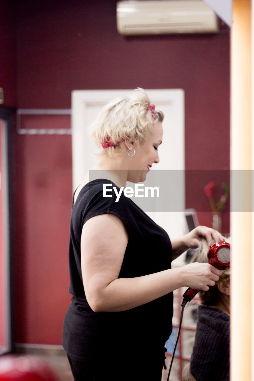 Side view of hairdresser styling female customer hair in salon