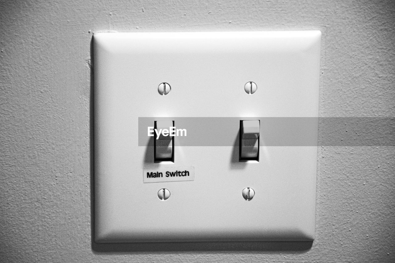 control, electricity, wall - building feature, indoors, connection, no people, light switch, close-up, switch, communication, technology, text, push button, white color, western script, outlet, convenience, power supply, bathroom, representation, electrical equipment