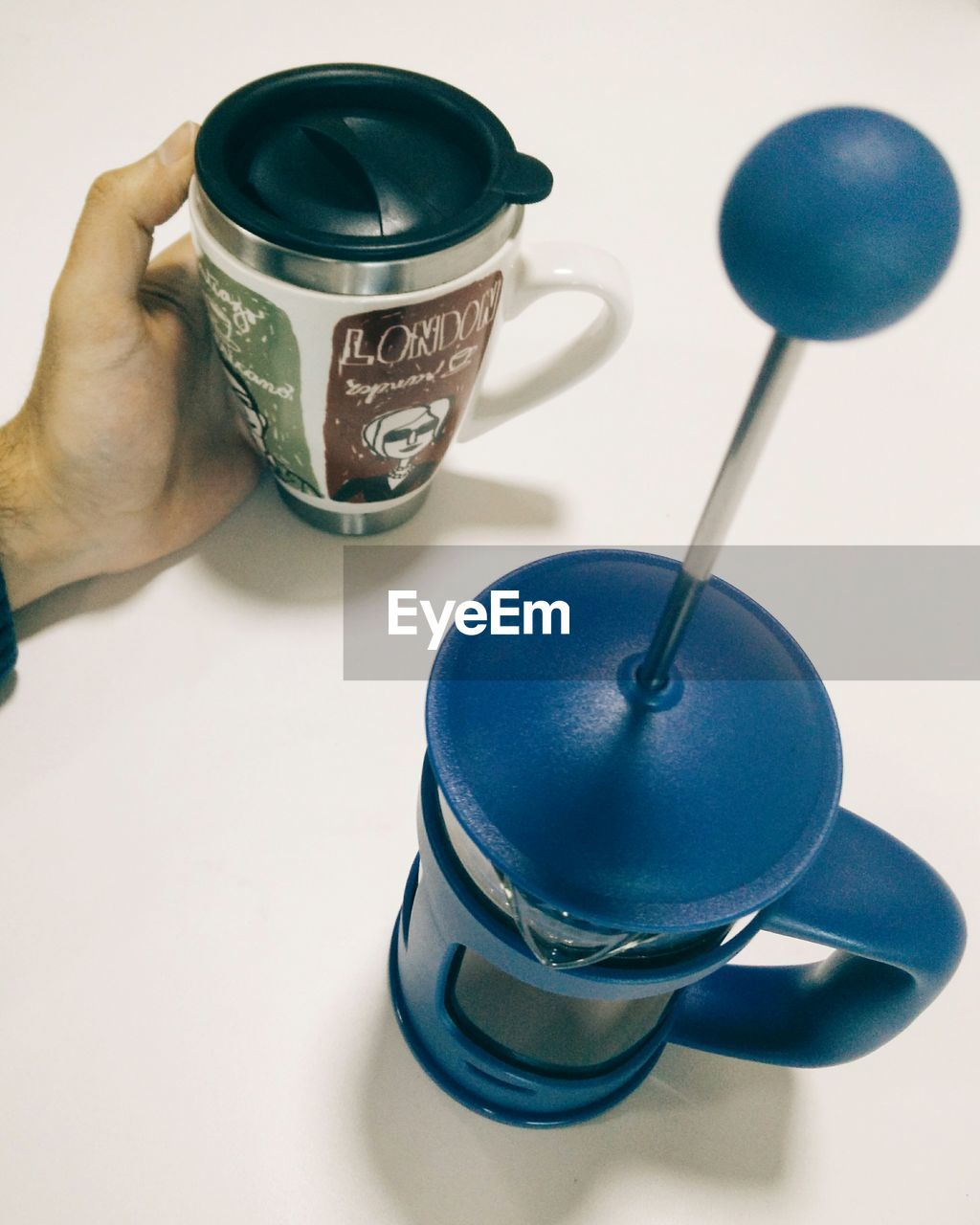 CLOSE-UP OF HAND HOLDING COFFEE CUP WITH SPOON