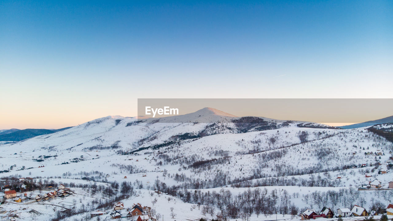 winter, cold temperature, snow, mountain, sky, scenics - nature, beauty in nature, environment, copy space, nature, tranquil scene, clear sky, landscape, tranquility, mountain range, snowcapped mountain, non-urban scene, covering, travel, outdoors