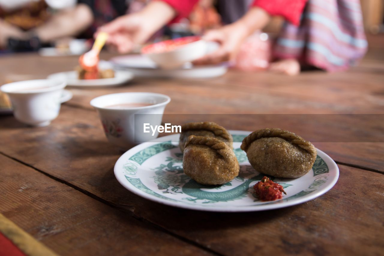 table, food and drink, food, indoors, freshness, baked, plate, real people, bowl, focus on foreground, still life, wood - material, ready-to-eat, selective focus, incidental people, cookie, people, group of people, sweet food, women, temptation, breakfast