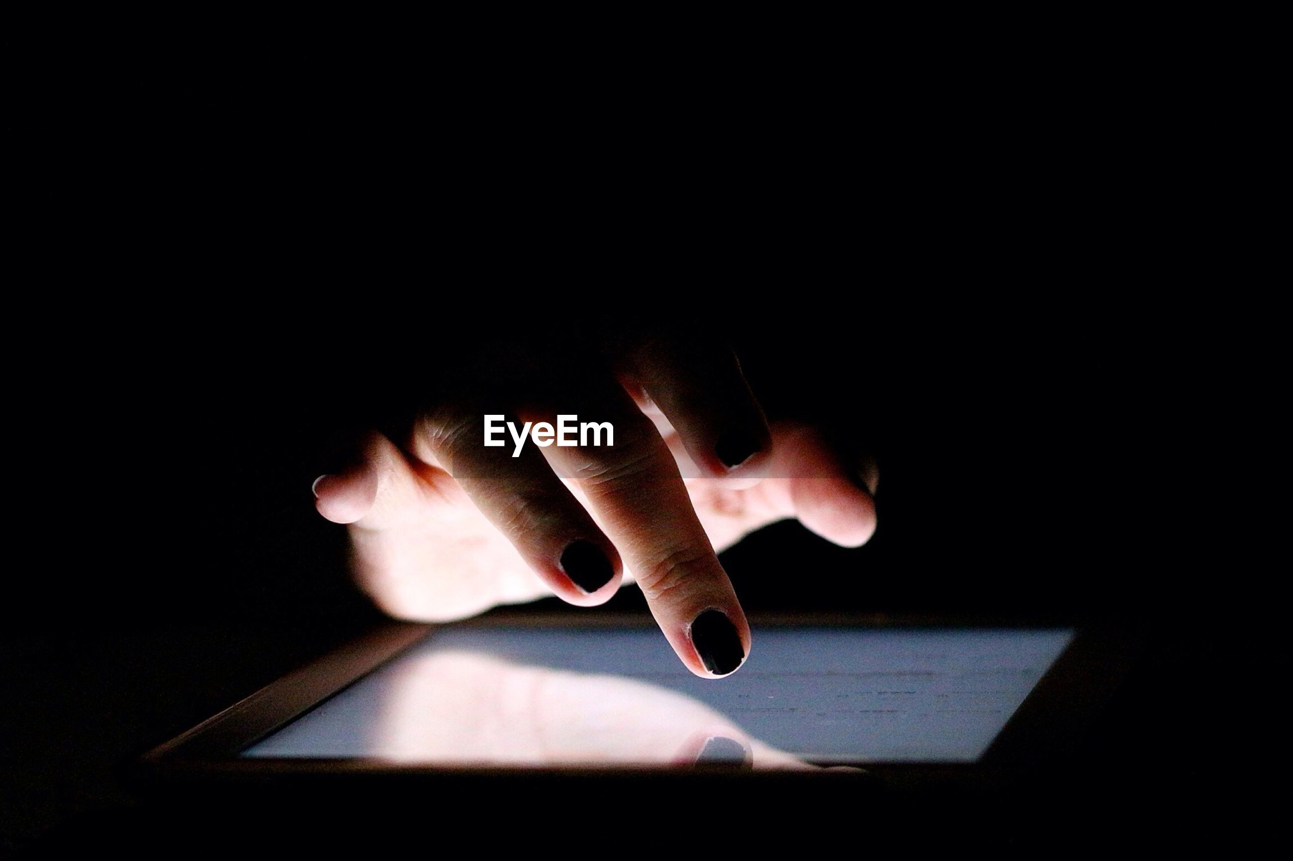 Cropped image of female hand touching digital tablet over black background