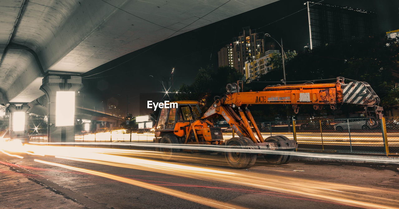 transportation, motion, industry, architecture, built structure, road, city, illuminated, mode of transportation, machinery, no people, blurred motion, long exposure, building exterior, street, night, land vehicle, rail transportation, speed, outdoors, industrial equipment, construction equipment