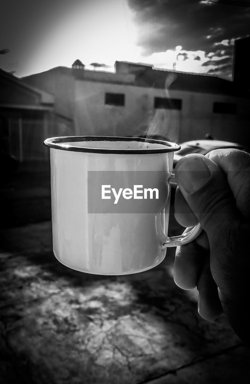 human hand, hand, holding, human body part, real people, one person, drink, cup, food and drink, refreshment, lifestyles, unrecognizable person, mug, personal perspective, focus on foreground, body part, coffee cup, close-up, indoors, finger, tea cup, glass, drinking