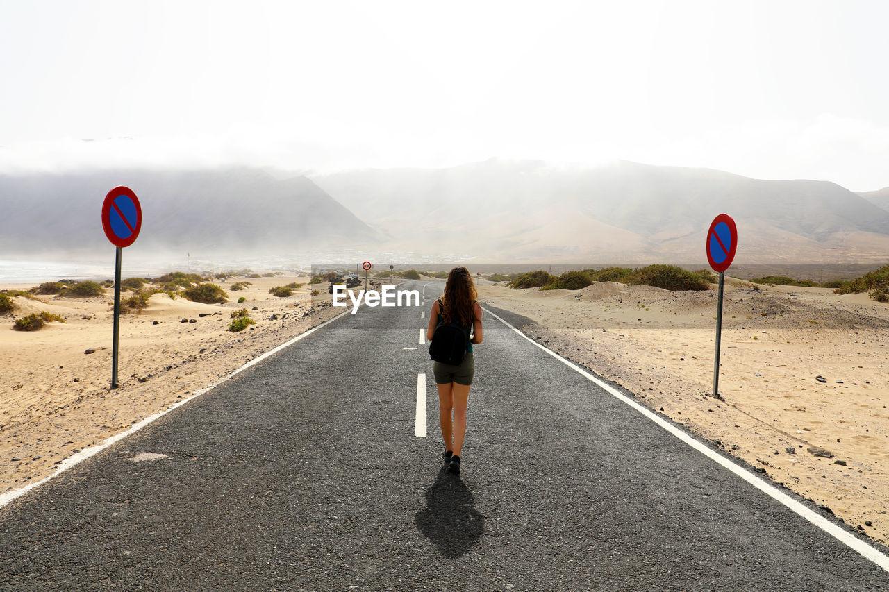 Rear View Full Length Of Woman Walking Amidst Field On Road