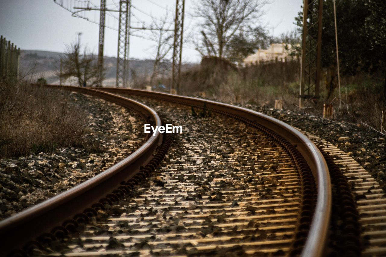 track, railroad track, rail transportation, tree, transportation, no people, metal, the way forward, nature, direction, plant, day, gravel, tranquility, travel, mode of transportation, public transportation, sky, bare tree, curve, surface level, long, parallel